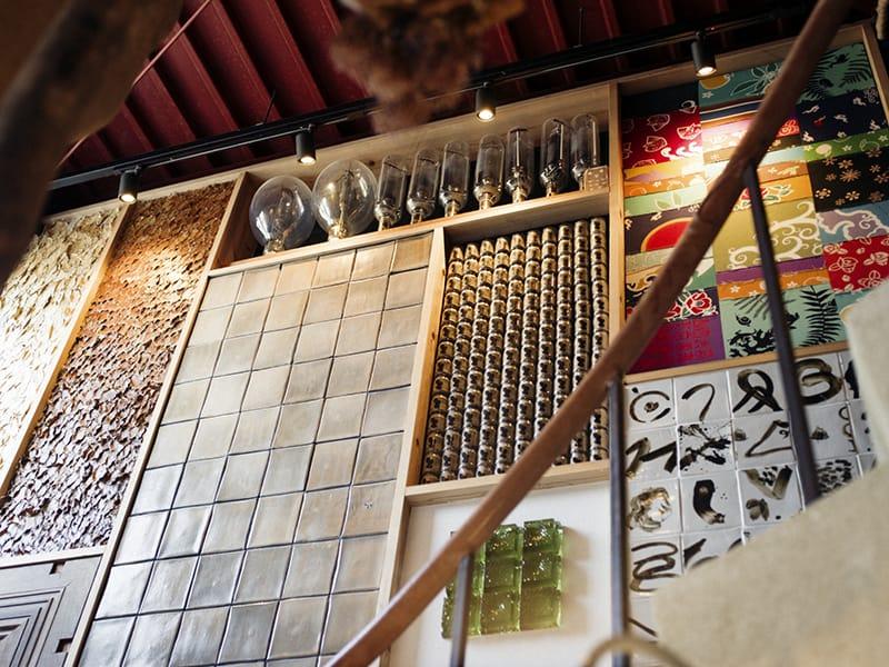 2階に上がる階段の壁一面には、萩にちなんだ素材がぎっしり埋め込まれている。萩焼の窯元「大屋窯」オリジナルのタイルや、萩ガラス、大漁旗のハギレなど。
