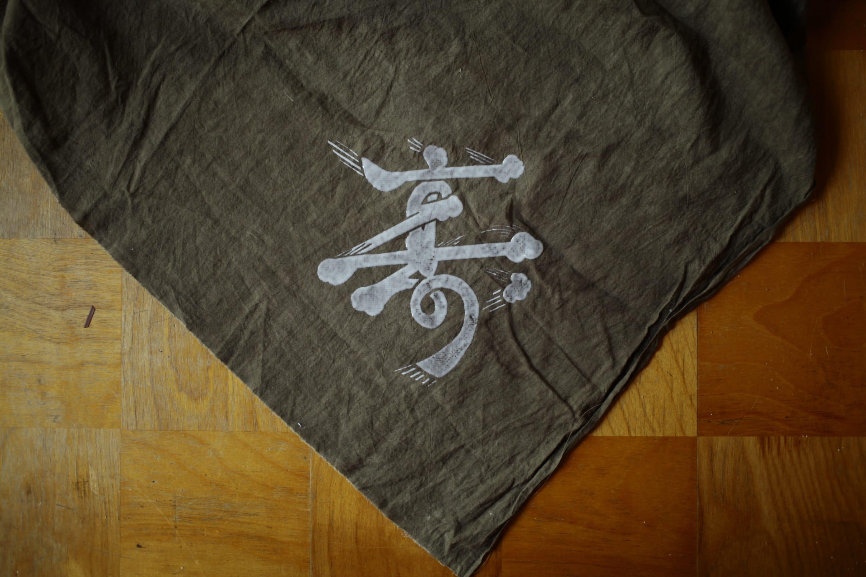 髭文字の型紙を作り、よもぎで染めたふろしき。