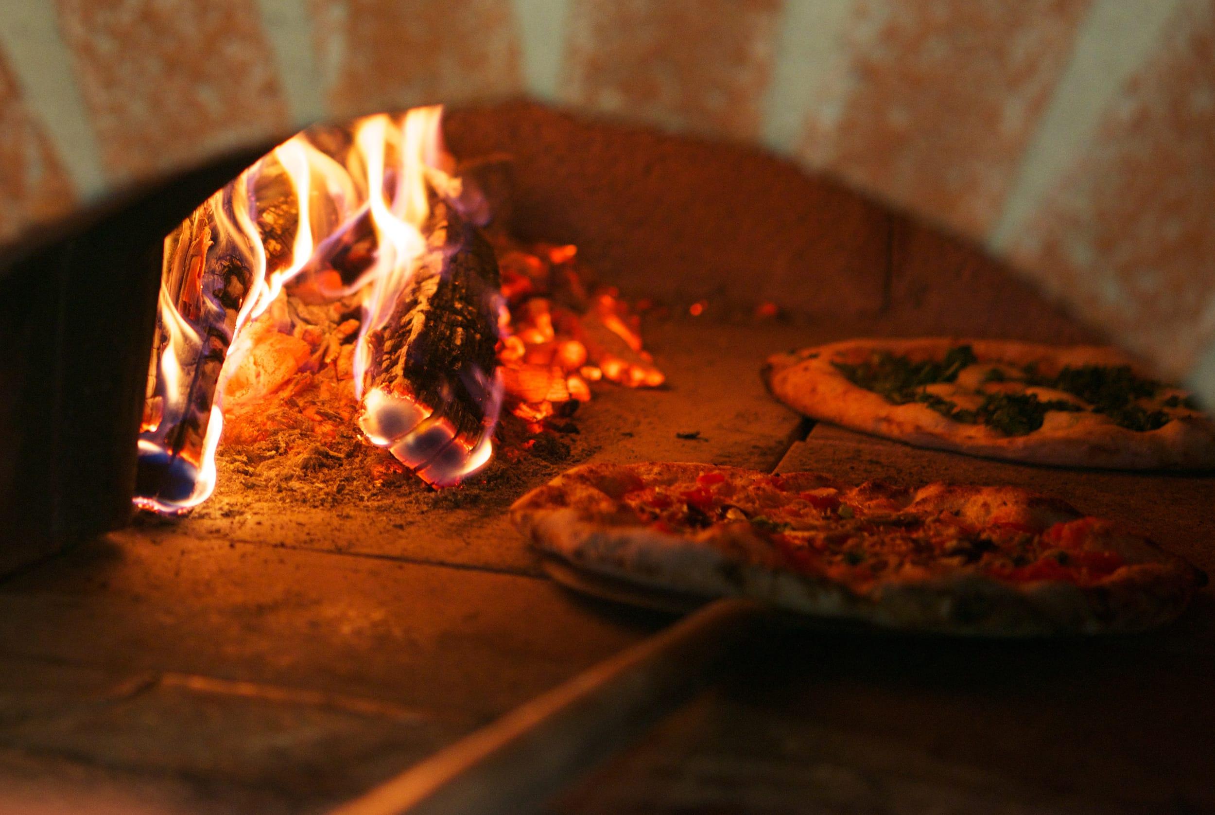 薄く伸ばした生地に具材をのせ、石窯で一気に焼き上げる。もちっと食べごたえのある生地は、すべて手捏ね。