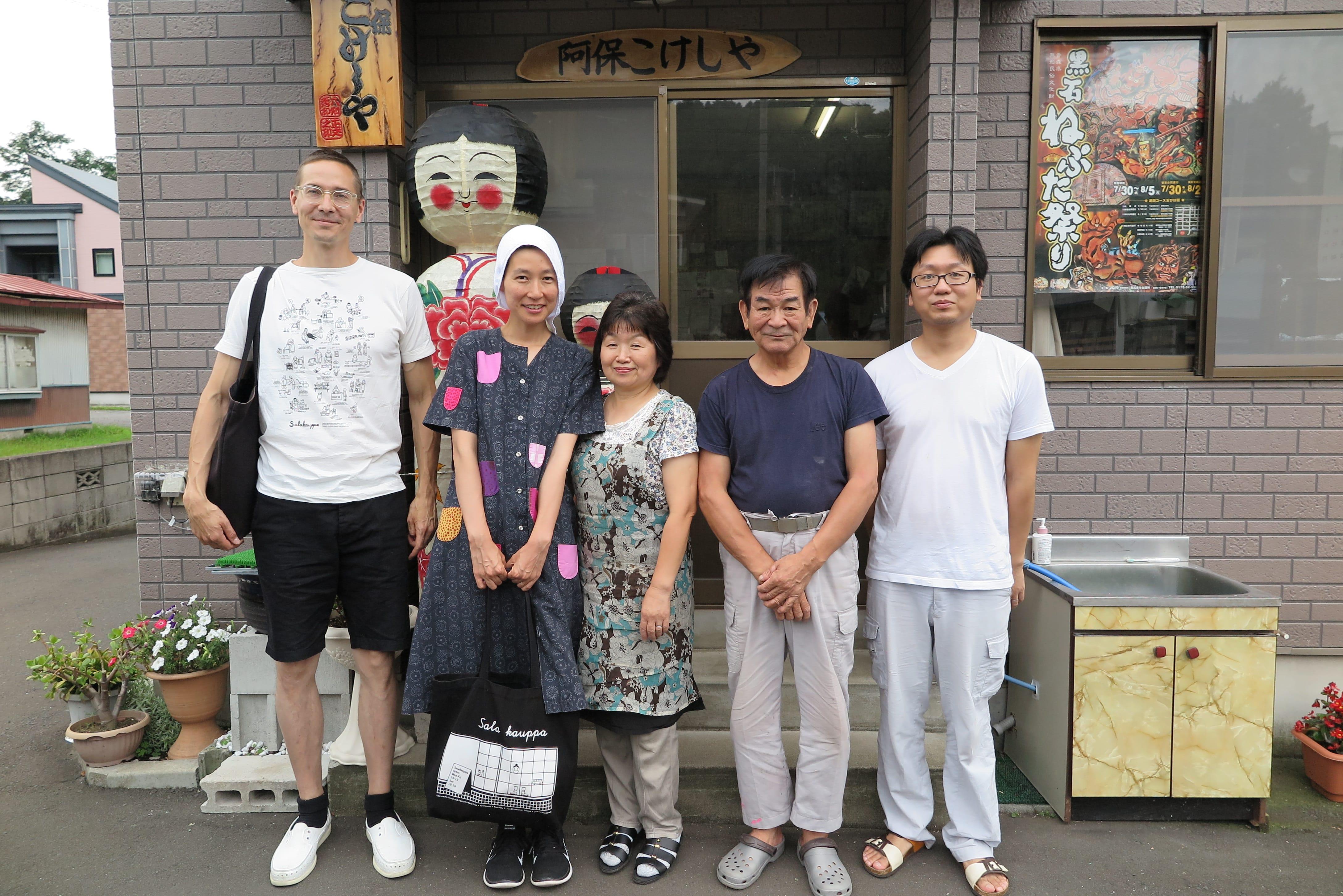 黒石市「阿保こけしや」の前で、工人・阿保六知秀氏とその家族とともに
