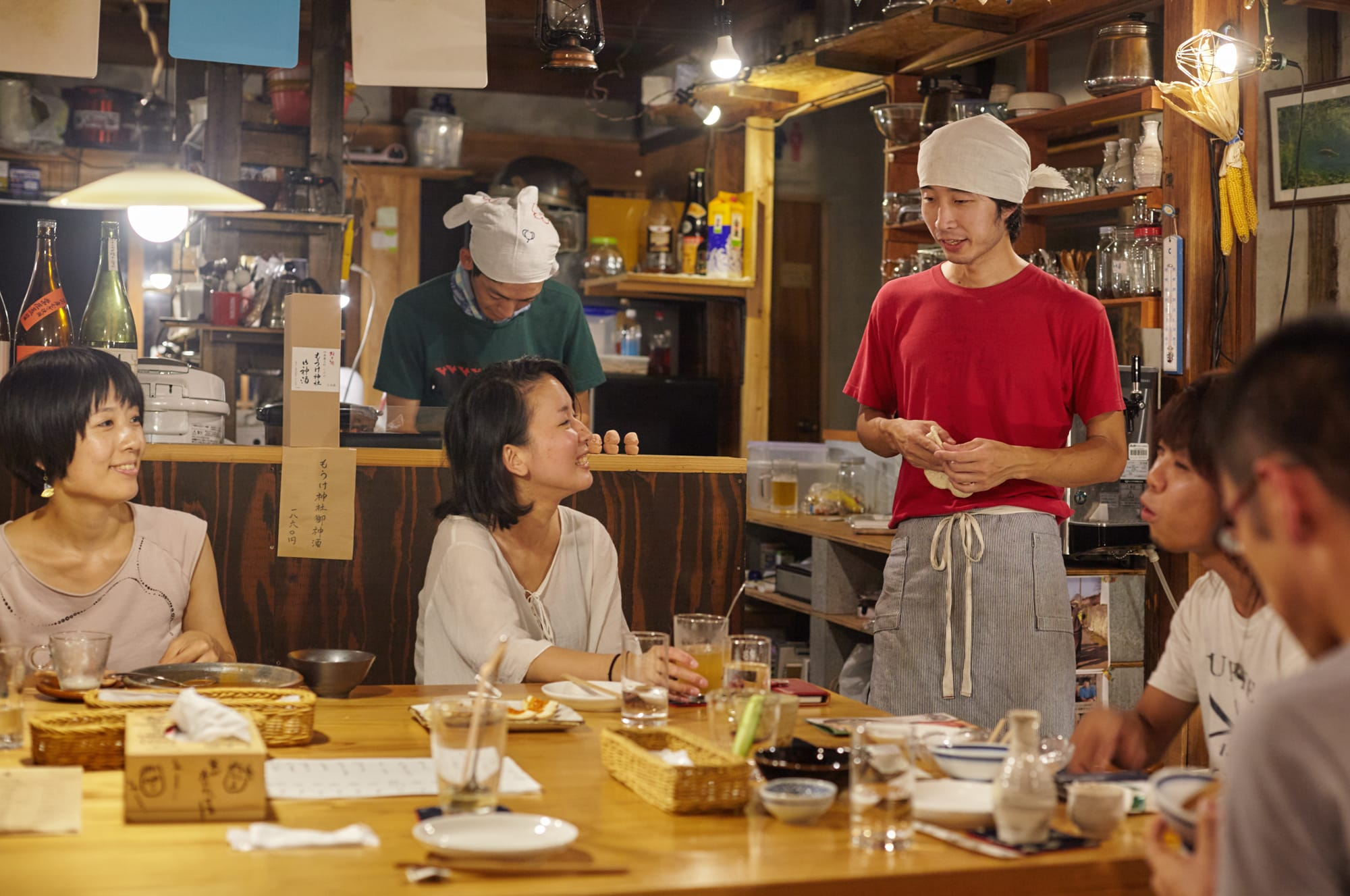 さまざまな出会いを生んだ場所「八百屋barものがたり」。料理は鹿野を代表する食材を使った料理を提供している。赤いシャツを着ているのが店長の成瀬 望さん。
