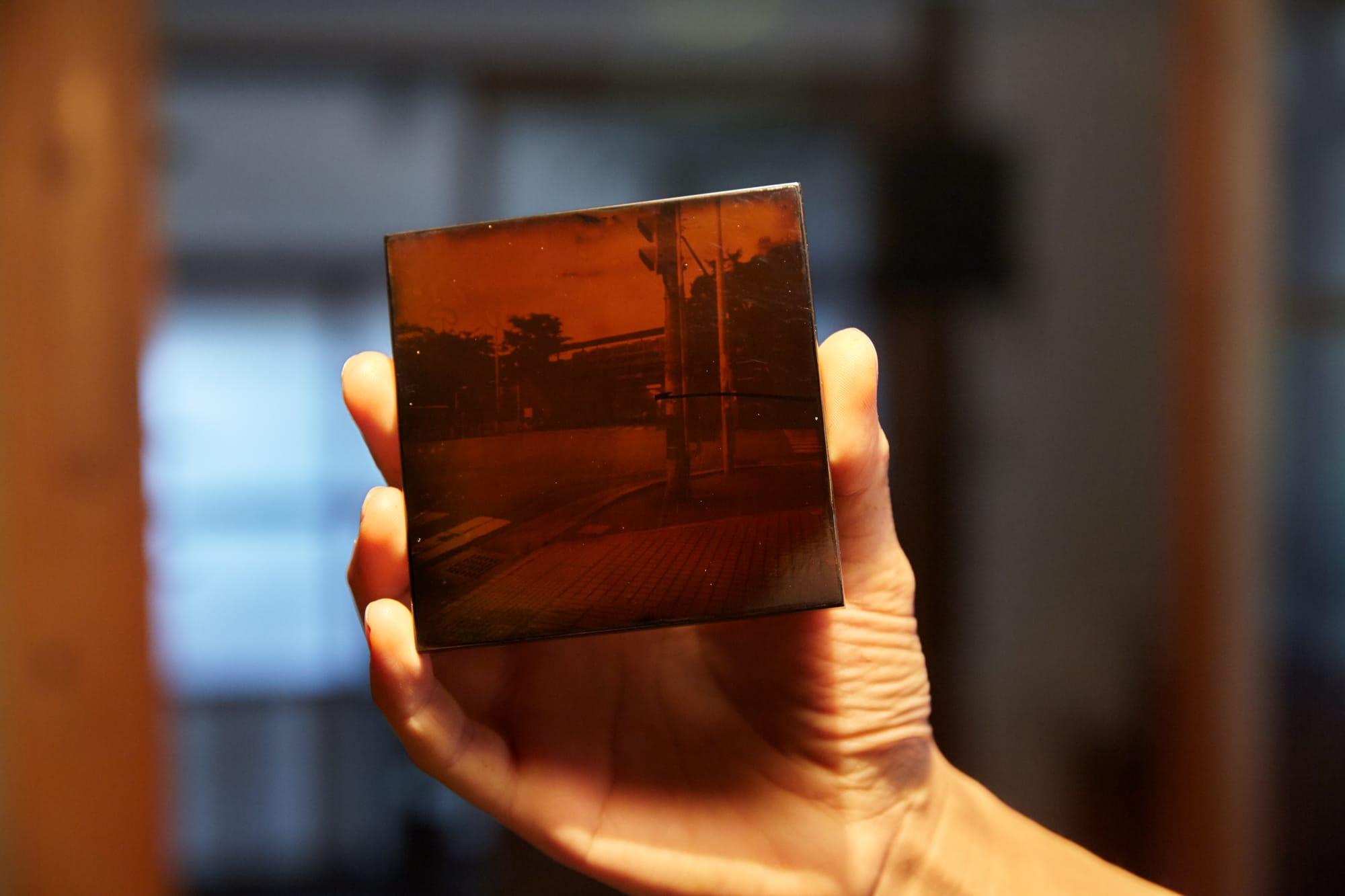 キヤノン写真新世紀の入選作は漆の板に感光性をもたせ、ピンホールカメラで風景を焼きつけたもの。写真は入選作と同じ方法でつくったテストピース。光を反射させると、漆黒の板の上に風景が浮かび上がる。