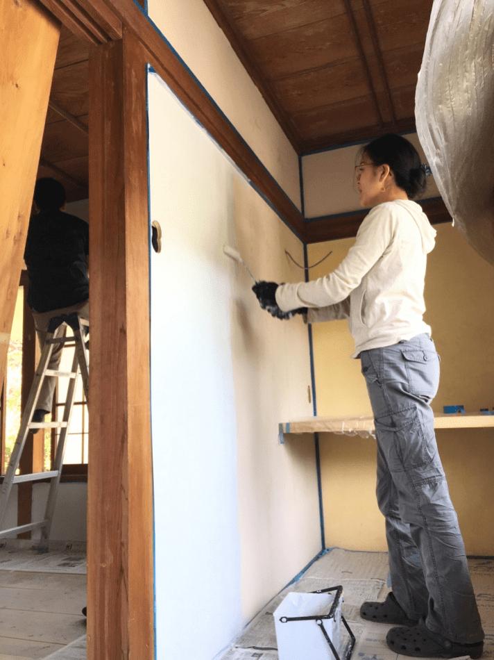 鬼籠野のすみはじめ住宅「西分の家」で壁塗りをしている高田さん。ものすごく真剣な面持ちです!(神山つなぐ公社提供)