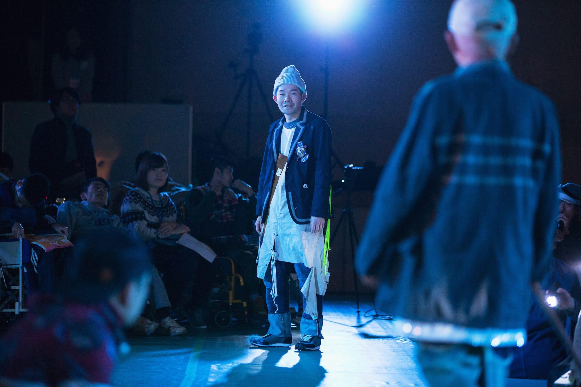 本番中の菅原直樹さんの様子。『オールライトファッションショー』では、円形に区切られた客席の合間を縫ってランウェイ=ステージが設けられた。ショーの企画制作・プロデュースは金森香さん。