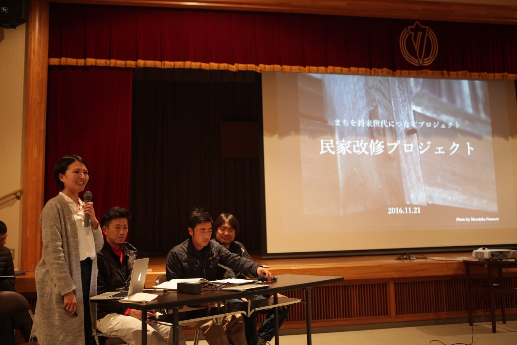 2016年11月21日「つなぷろ発表会」で民家改修プロジェクトについて、町内の工務チーム(右から製材屋さん、中央、左は若手大工さん)とともに報告する赤尾さん。