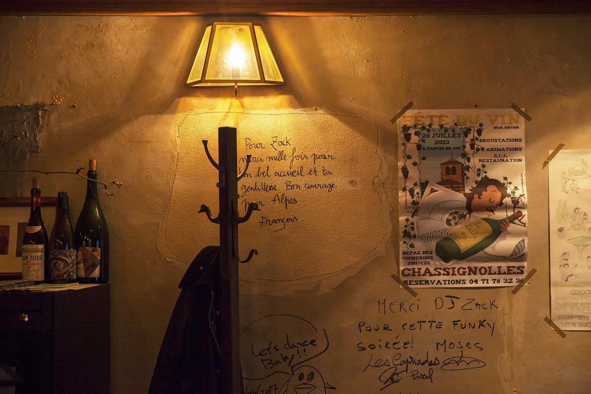 内装は池崎さんの地元の友人にも手伝ってもらい、ほぼDIYで改装。レトロな深紅の木枠をアンティーク調のダークブラウンに塗り替え、カウンターは立ち飲みできる高さに上げ、仕上げに荒井さんのアイデアで壁紙を剥がした。写真は改装中にフランスから訪ねてきたサヴォワ地方の生産者フランソワ・グリナン氏が壁に書いたサイン。ここだけ壁紙が残されている。