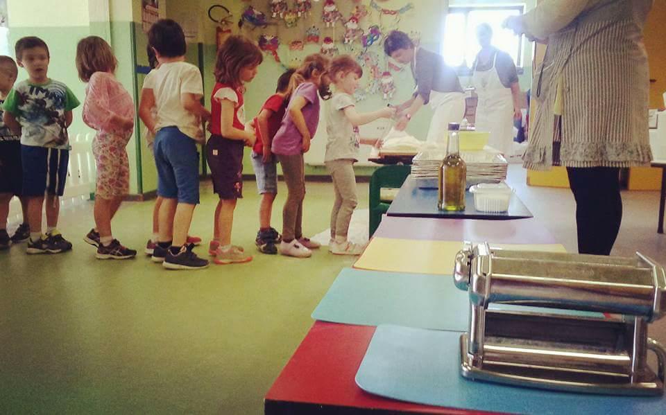 ヴェルドゥーノのレストランのシェフと一緒に幼稚園で食育の授業をする川本さん。食育の取り組みは、イタリアで学び買ったことのひとつでした(川本さん提供)。