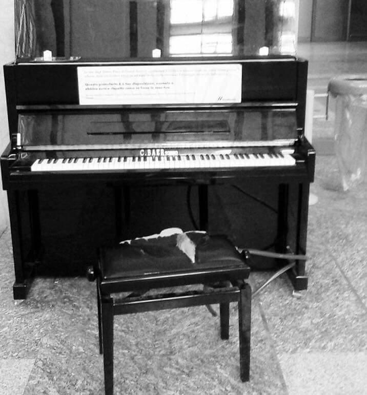 トリノ駅で川本さんが弾いていたピアノ。盗難防止のためチェーンでつながれたイス、綿が飛び出している(川本さん提供)。