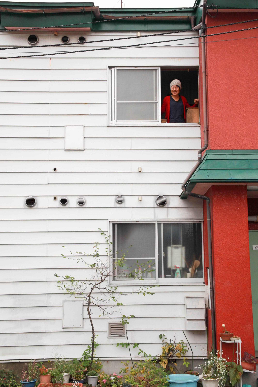 自宅の窓から顔を出す川地さん。色合いがかわいらしい建物は築20年弱の建物。