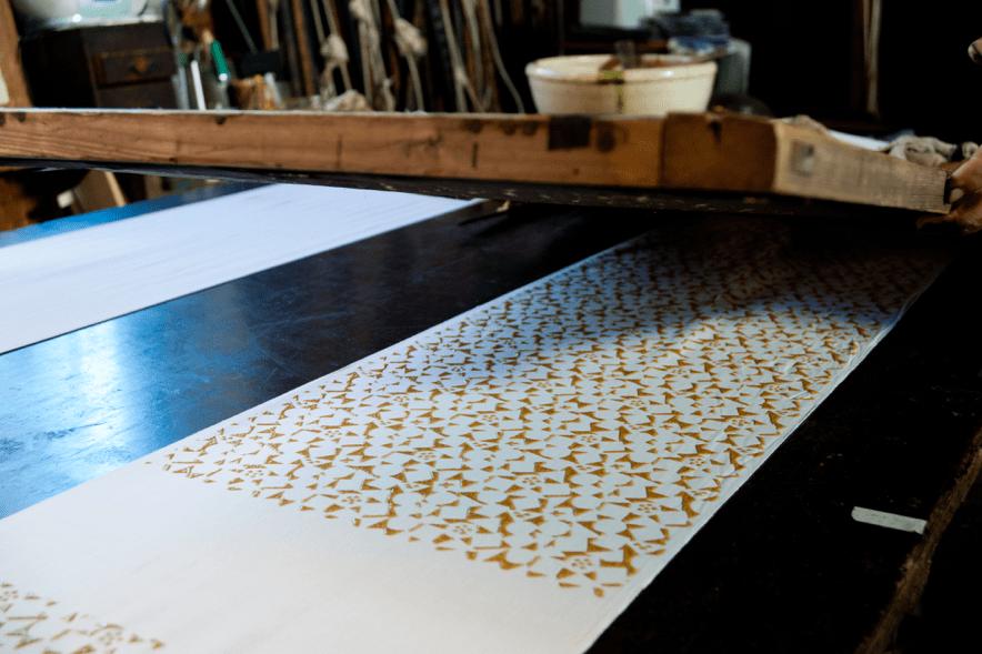 もち粉と米ぬかを原材料に作った糊で、生地に型をのせていく。
