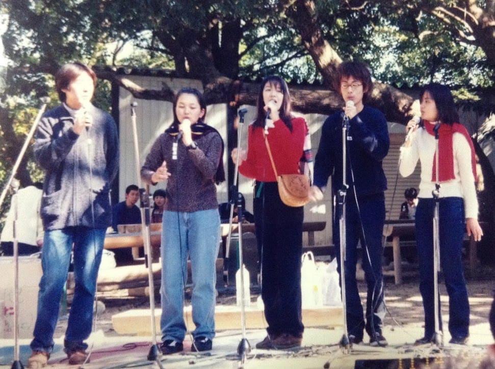 大学時代、アカペラサークルでも歌っていました(中央)。学祭のステージにて。