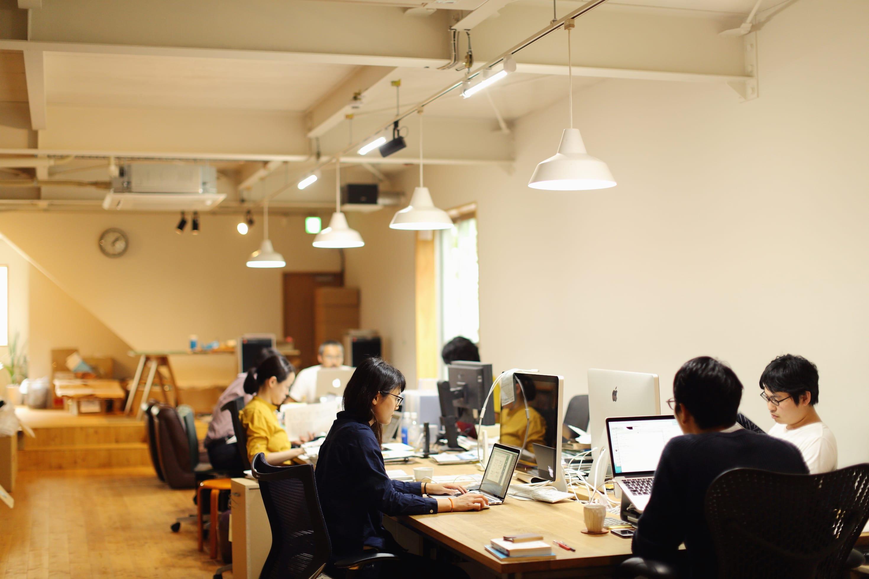 とんがりビルの2階にある「アカオニ」のオフィス。ひとつの大きなテーブルをスタッフみんなで囲んで仕事をする。