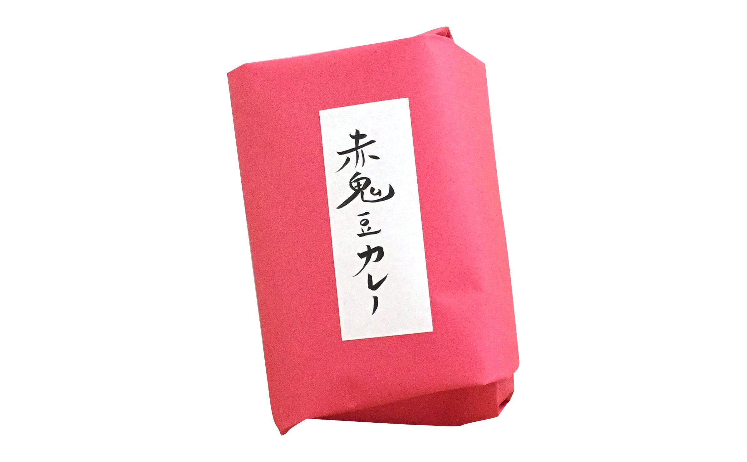2016年の山形ビエンナーレ「みちのおく商店」で販売した「赤鬼豆カレー」。真室川産の伝承豆や古代米、スパイスなどが赤い紙で包まれています。商品名は一枚ずつ手書き。にじみ出る味が素敵。(難波)