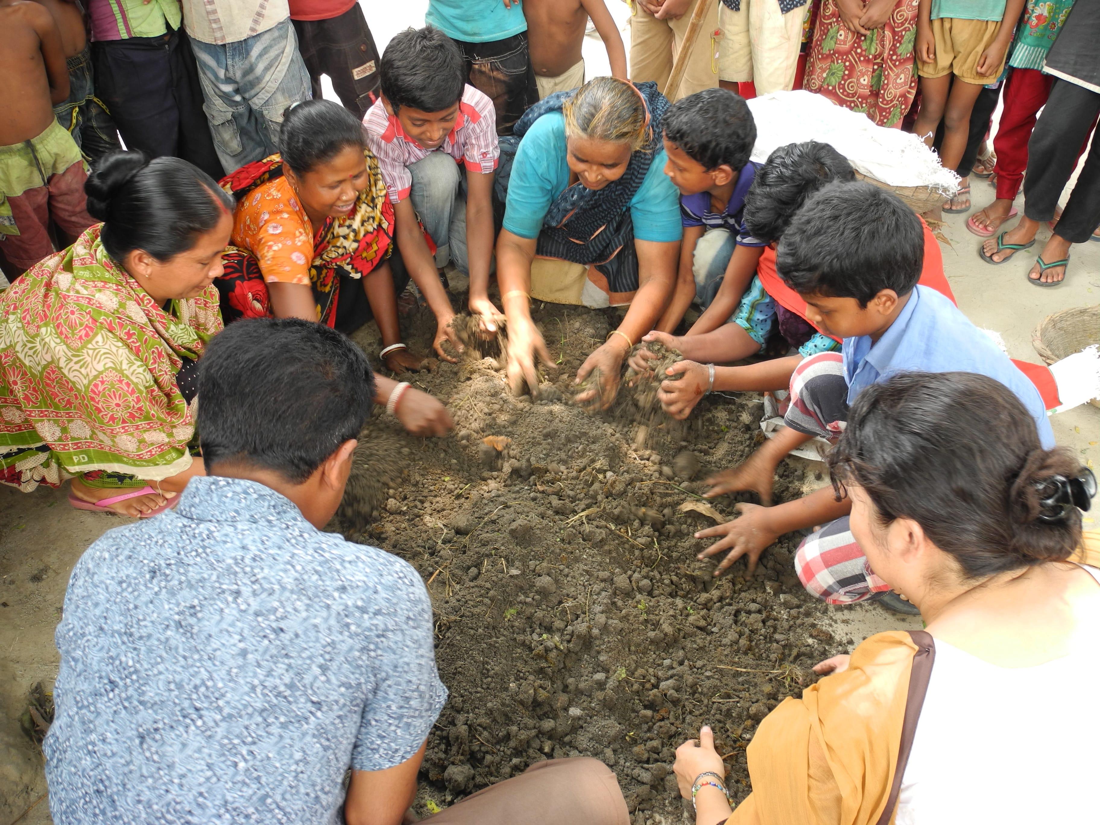 袋で野菜を栽培する方法を教えるワークショップ。土をつくっています(モジャさんは右端、後姿)