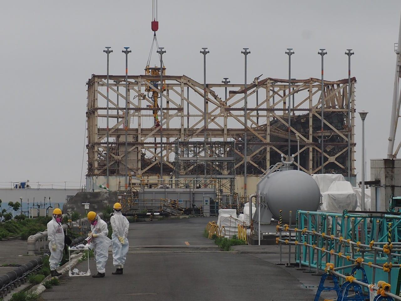 原子炉建屋前ではフル装備の作業員が作業にあたる。