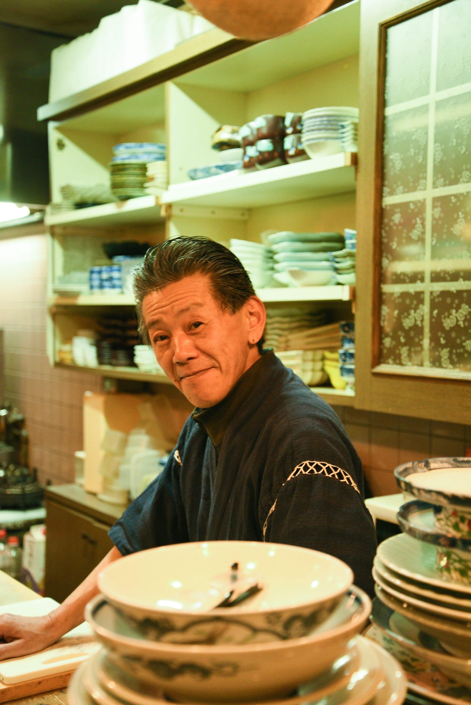 飲み屋巡りの1軒目に訪れた居酒屋「ほのか」の大将。旬の地魚を使った一品料理が豊富で、地元の常連さんが仕事帰りに集う憩いの場。