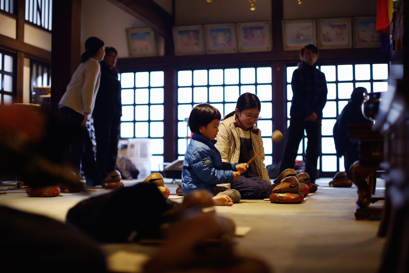 大切そうに木魚を抱えて仏前に座る3歳の男の子も。大人も並んで座り、木魚を叩きながらの読経。井上さんに続いて読み上げるにつれて集中力が高まる。
